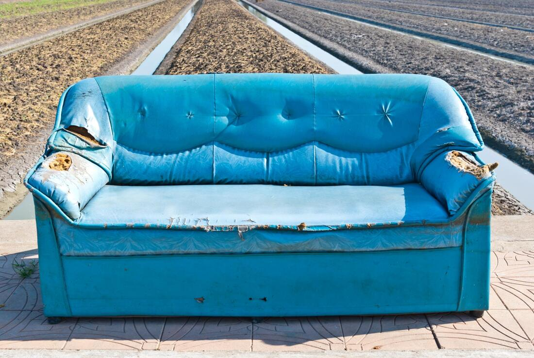 sofa left outside waiting to be removed